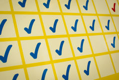 Blue and red checkmarks in yellow grid. Detail of blue and red checkmarks in yellow grid Royalty Free Stock Photo