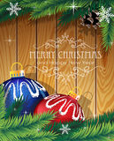Blue and red Christmas balls on wooden background. Blue and red Christmas balls, fir tree branches and cone on wooden background Stock Photo