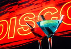 Blue and red cocktail with neon disco word background with space for text Royalty Free Stock Photo