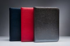 Blue, red and dark gold-silver leather notebook on grey background. Three notebooks with natural leather covers of blue, red and gold-silver colors, standing on Royalty Free Stock Photos