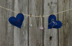 Blue and red fabric hearts and locks hanging on clothesline by rustic wooden background Stock Image
