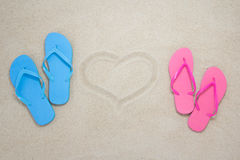 Blue, red flip flops and heart on beach Stock Photos