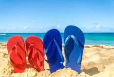 Blue and red flip flops on the sandy beach Stock Photo