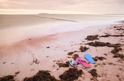 Blue red Flip Flops and white swimming goggles ready for using on stony beach at wooden breakwater. Stock Photography
