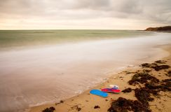 Blue red Flip Flops and white swimming goggles ready for using on stony beach at wooden breakwater. Stock Image