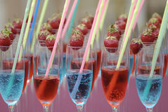 Blue red glasses with strawberries. Close-up of misted up wine glasses with blue and red drinks, coloured straws and strawberries on their edges royalty free stock photos