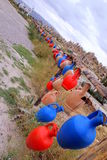 Blue and red handmade turkish jugs are hanging near to mountains. Royalty Free Stock Photography
