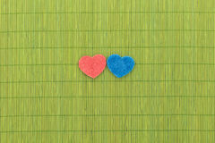 Blue and red hearts against bamboo sticks Royalty Free Stock Photography