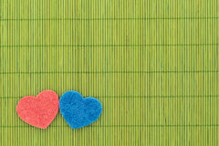 Blue and red hearts against bamboo sticks Royalty Free Stock Photos