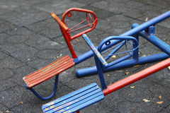 Blue and red horse shaped seesaws. In public playground Royalty Free Stock Photos