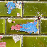 Blue and red paint peeling off green ceramic wall tiles Stock Image