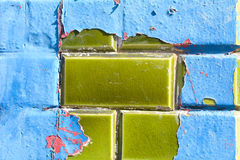 Blue and red paint peeling off green ceramic wall tiles Stock Photos