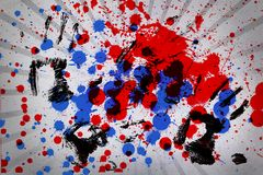 Blue and red paint splashes with black hand prints Stock Photos
