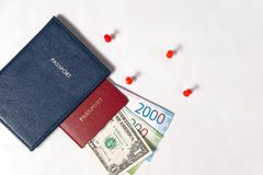 Blue and red passport with the dollar and the new Russian banknotes rubles or euros on a white background with red pins Royalty Free Stock Image