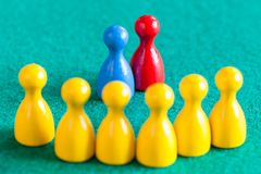 Blue and red pawns in front of yellow pawns stock photography