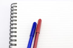 Blue and red pen with notebook isolated on white Royalty Free Stock Photo