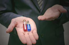 Blue and red pill essential liquid in business man hands. Choosing of right pill. stock photo
