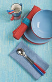 Blue and red plates. Top view of the kitchen utensils: red and blue plates, cups, spoons and napkins on a blue cracked background Stock Photos