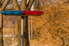 Blue and red police lights. Closeup of blue and red police lights on metal stand with electrical lines in front of tree Royalty Free Stock Photo