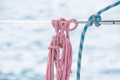 Blue and red ropes on a yacht bar Stock Image