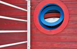 Blue and Red Round Window in a Red Wooden Wall Royalty Free Stock Photo