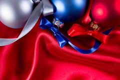 Blue, red and silver christmas balls on a silk cloth Stock Image