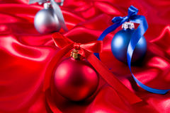 Blue, red and silver christmas balls on a silk cloth Stock Photos