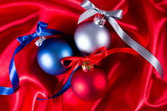 Blue, red and silver christmas balls on a silk cloth Royalty Free Stock Photography