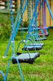 Blue and red swings hanging in the park Royalty Free Stock Photo