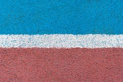 Blue - red tartan surface of athletics stadium with white horizontal line royalty free stock photos