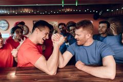 Blue and red team fans arm wrestling at sports bar with fans in background. royalty free stock photo