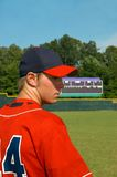 Blue and Red Team Player. Male teen looks sideways with scoreboard in background.  He has on red and blue uniform.  Baseball field fills background Stock Images