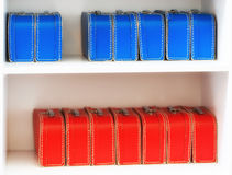 Blue and red toy cases on the shelf background Royalty Free Stock Photos