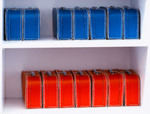 Blue and red toy cases on the shelf background Stock Images