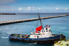 Blue and Red Tugboat in Blue Harbor Stock Photos