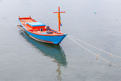 Blue and red vacant fisherman's rowboat floating on sea, tradi Royalty Free Stock Photography