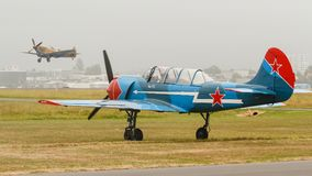 A blue and red Yak-52 trainer aircraft on the ground stock images