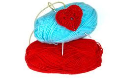 Blue and red yarn with needls and knitted red heart. Royalty Free Stock Photography