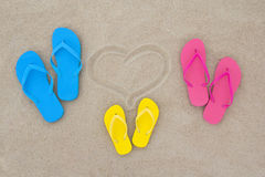 Blue, red, yellow flip flops and heart on beach Royalty Free Stock Photography