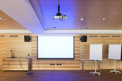 Blue reflections of video projector. In wooden conference room stock images
