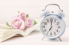 Blue retro alarm clock with book and pink pastel roses stock photos