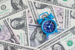 Blue retro alarm clock on US dollar banknotes as money time conc. Ept Stock Photos