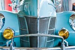 Blue retro car with yellow headlamps Stock Photos