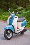Blue retro scooter in the forest with helmet.  Royalty Free Stock Images