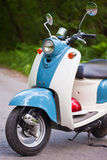 Blue retro scooter in the forest with helmet.  Stock Photos