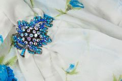 Blue rhinestone brooch on a white and blue silk scarf, copy space. Horizontal aspect Royalty Free Stock Photo