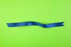 Blue ribbon. On green background stock photography