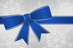 Blue Ribbon Bow. Blue and silver ribbon bow on snowflake background for Hanukkah, Christmas or winter holidays Stock Photos