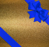 Blue ribbon and bow over shiny golden background Royalty Free Stock Images
