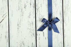 Blue ribbon with bow on white wooden background. Royalty Free Stock Photography